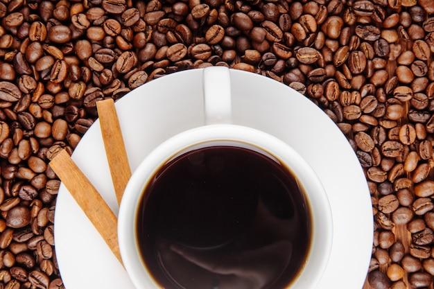 Bovenaanzicht van een kopje koffie met krokante stokken op koffiebonen achtergrond
