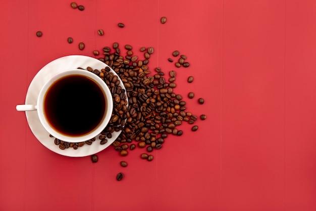 Bovenaanzicht van een kopje koffie met vers gebrande koffiebonen geïsoleerd op een rode achtergrond met kopie ruimte