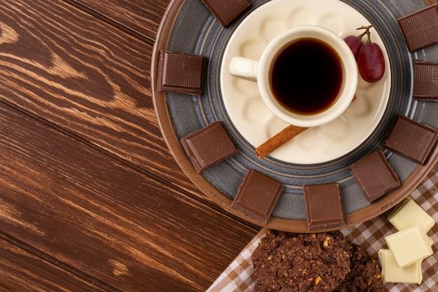 Bovenaanzicht van een kopje koffie met witte en donkere chocolade en havermout koekjes op houten achtergrond met kopie ruimte