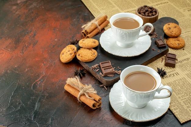 Bovenaanzicht van een kopje koffie op een houten snijplank op een oude krant, koekjes, kaneellimoenen, chocoladerepen aan de linkerkant