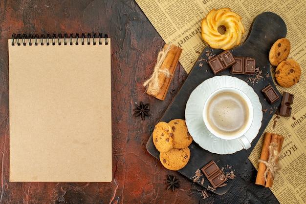 Bovenaanzicht van een kopje koffie op een houten snijplank op een oude krant, koekjes, kaneellimoenen, chocoladerepen, notitieboekje op een donkere ondergrond