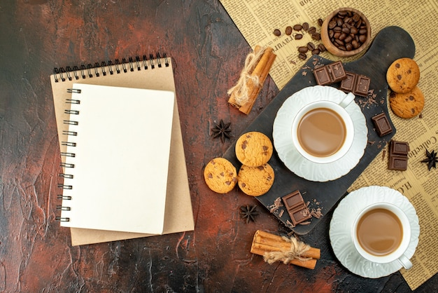 Bovenaanzicht van een kopje koffie op een houten snijplank op een oude krant, koekjes, kaneellimoenen, chocoladerepen, spiraalvormig notitieboekje