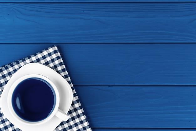 Bovenaanzicht van een kopje koffie op schotel op klassieke blauwe achtergrond