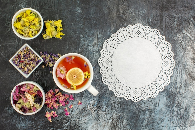Bovenaanzicht van een kopje kruidenthee met kommen met droge bloemen en kant op grijze achtergrond