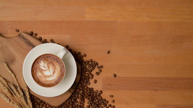 Bovenaanzicht van een kopje latte-koffie op houten tafel versierd met koffiebonen, placemat en kopie ruimte