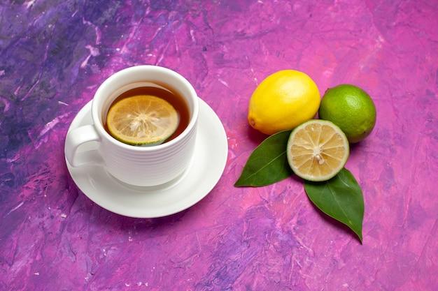 Bovenaanzicht van een kopje thee citrusvruchten met bladeren naast het kopje smakelijke thee met citroen op de paars-roze tafel