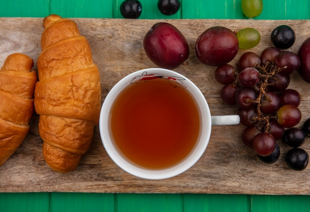 Bovenaanzicht van een kopje thee en croissants met druivenplukken en sleedoornbessen op snijplank op groene achtergrond