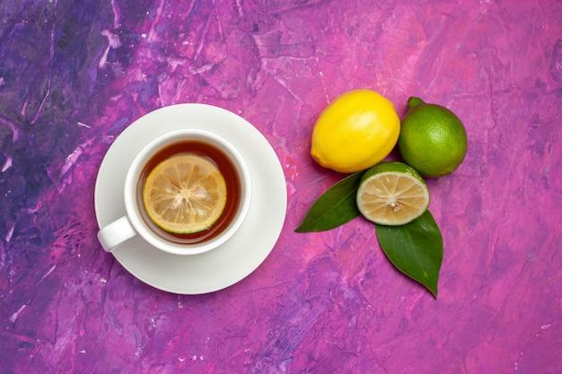Bovenaanzicht van een kopje thee limoenen en citroen met bladeren naast het kopje smakelijke thee met citroen op de paars-roze tafel