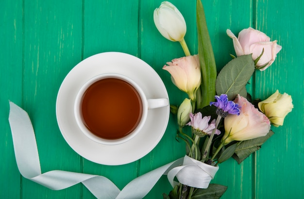 Bovenaanzicht van een kopje thee met bloemen zoals daisy rose en tulp op een groene houten achtergrond
