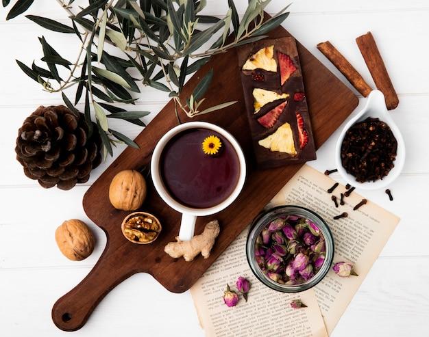 Bovenaanzicht van een kopje thee met chocoladereep met gedroogde vruchten en hele walnoten op houten snijplank, droge rozenknoppen in een glazen pot en kruidnagel op wit