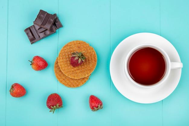Bovenaanzicht van een kopje thee met chocoladereep wafels en aardbeien op blauw
