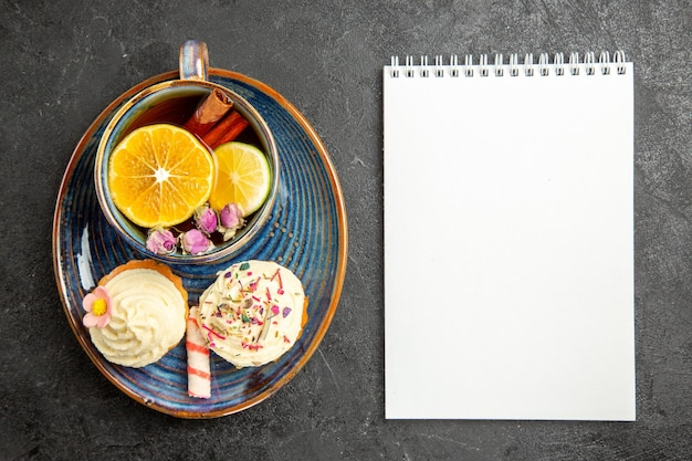 Bovenaanzicht van een kopje thee met citroen de smakelijke cupcakes met room naast het kopje kruidenthee met citroen en kaneel en wit notitieboekje op de donkere tafel