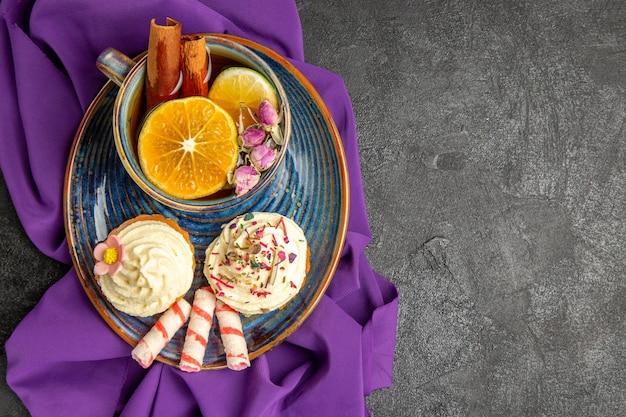 Bovenaanzicht van een kopje thee met citroenplaat van de smakelijke cupcakes en een kopje thee op het paarse tafelkleed aan de linkerkant van de tafel