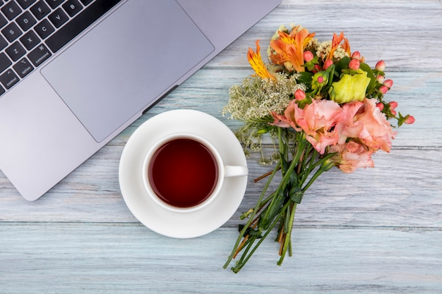 Bovenaanzicht van een kopje thee met een boeket van prachtige bloemen op grijs hout