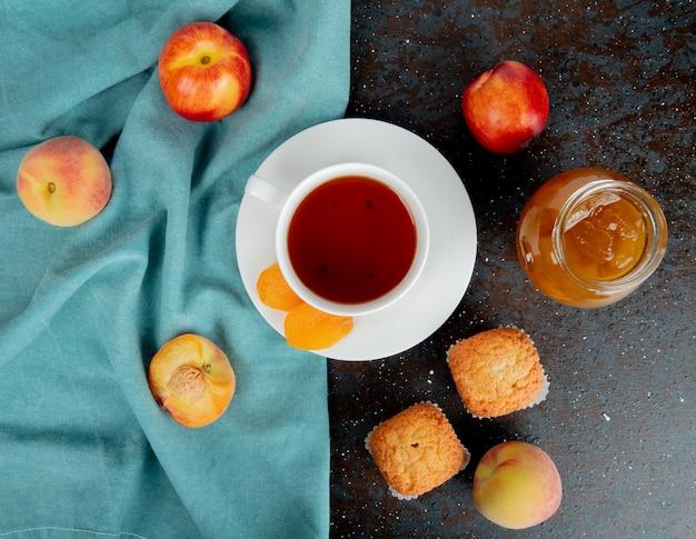 Bovenaanzicht van een kopje thee met gedroogde abrikozen en verse rijpe perziken op blauwe stof en muffins met een glazen pot met perzikjam op zwart