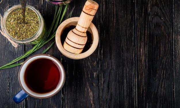 Bovenaanzicht van een kopje thee met gedroogde pepermunt in een glazen pot en zwarte peperkorrels in een houten vijzel op zwart hout met kopie ruimte