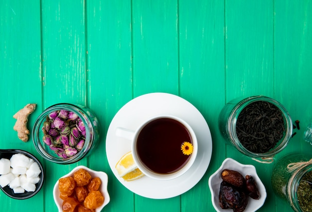 Bovenaanzicht van een kopje thee met gedroogde vruchten en droge rozenknoppen met zwarte theebladeren in glazen potten op groen hout met kopie ruimte