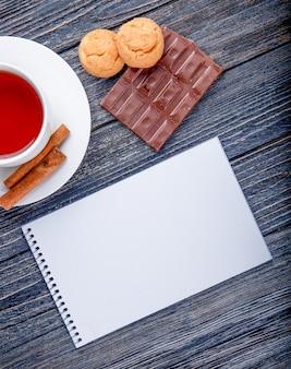 Bovenaanzicht van een kopje thee met kaneelstokjes sketchbook en donkere chocolade met koekjes op rustieke achtergrond
