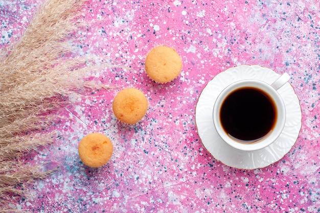 Bovenaanzicht van een kopje thee met kleine cakes op het roze oppervlak