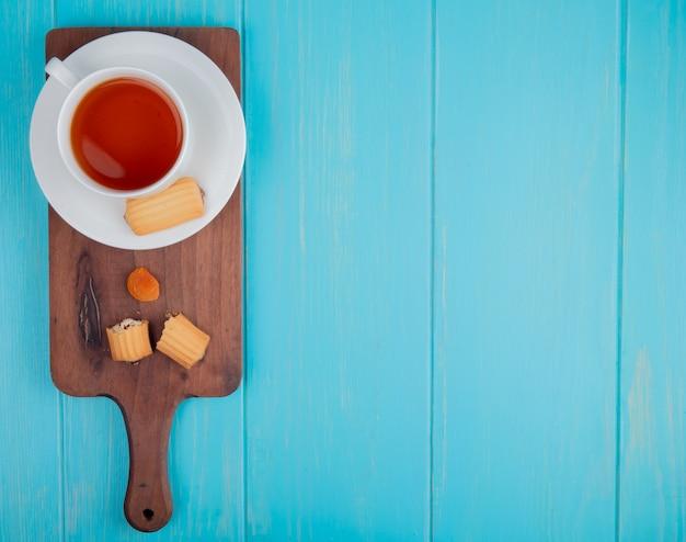 Bovenaanzicht van een kopje thee met koekjes en gedroogde abrikoos op houten snijplank op blauw met kopie ruimte