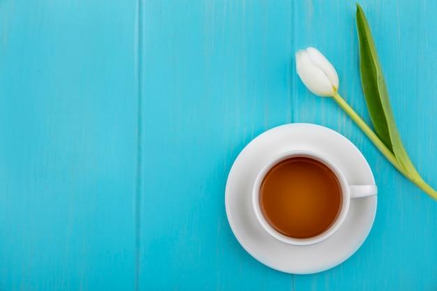 Bovenaanzicht van een kopje thee met mooie witte tulp op een blauwe houten achtergrond met kopie ruimte