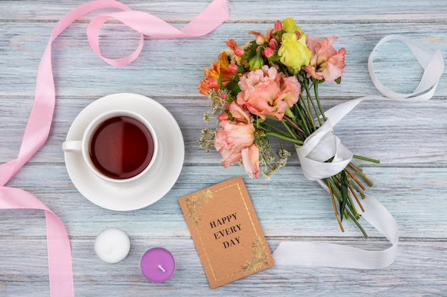 Bovenaanzicht van een kopje thee met prachtig gekleurd boeket bloemen gebonden met wit lint op grijs hout