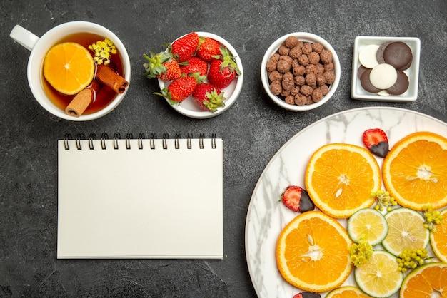 Bovenaanzicht van een kopje thee smakelijk gerecht van citrusvruchten en aardbeien naast de kommen chocolade aardbeien en hizelnoten wit notitieboekje en kopje thee met citroen