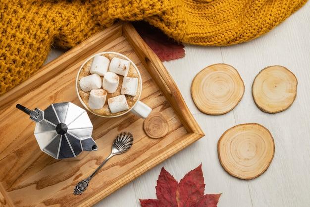 Bovenaanzicht van een kopje warme chocolademelk met marshmallows en een waterkoker