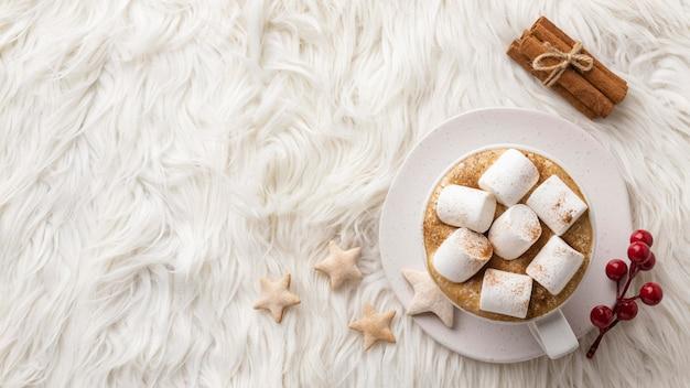 Bovenaanzicht van een kopje warme chocolademelk met marshmallows en kaneelstokjes