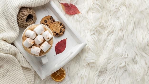 Bovenaanzicht van een kopje warme chocolademelk met marshmallows en koekjes