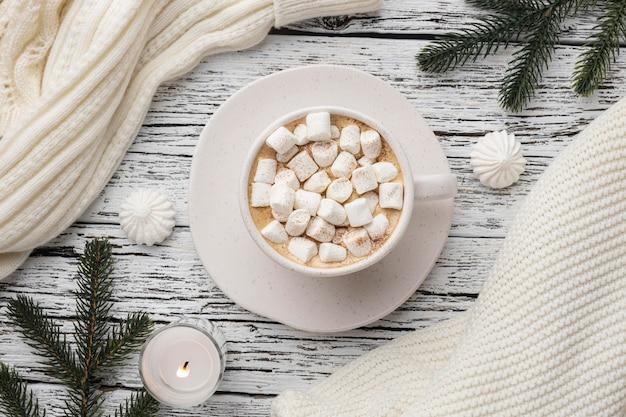 Bovenaanzicht van een kopje warme chocolademelk met marshmallows en trui
