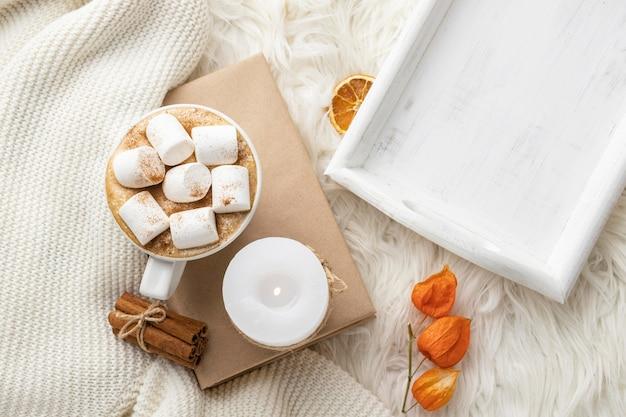 Bovenaanzicht van een kopje warme chocolademelk op boek met marshmallows en kaars
