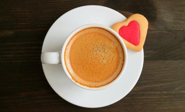 Bovenaanzicht van een kopje warme koffie met hart cookie op donkere houten tafel