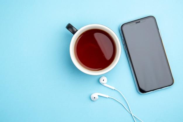 Bovenaanzicht van een kopje zwarte thee mobiele telefoon hoofdtelefoon op blauwe achtergrond