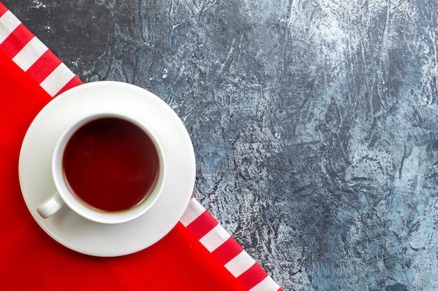 Bovenaanzicht van een kopje zwarte thee op een rode handdoek aan de rechterkant op een donkere ondergrond