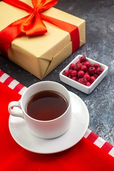Bovenaanzicht van een kopje zwarte thee op een rode handdoek en koekjes op een witte plaat cadeau met rood lint en cornel op donkere ondergrond