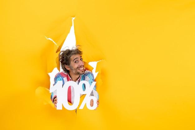 Bovenaanzicht van een lachende en positieve jongeman die tien procent in een gescheurd gat in geel papier toont