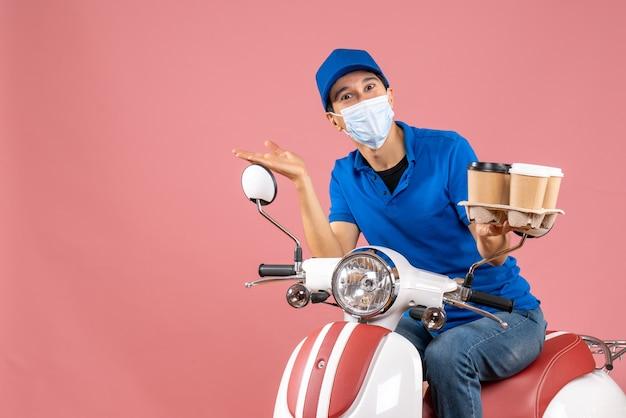 Bovenaanzicht van een lachende, gelukkige mannelijke bezorger met een masker met een hoed op een scooter die bestellingen aflevert op perzik