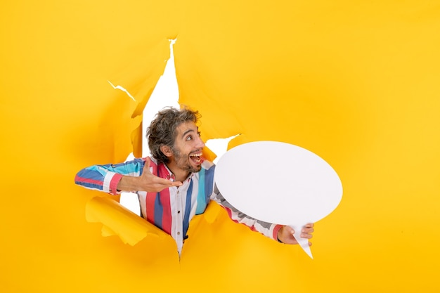 Bovenaanzicht van een lachende jongeman die een witte pagina aanwijst met vrije ruimte in een gescheurd gat in geel papier