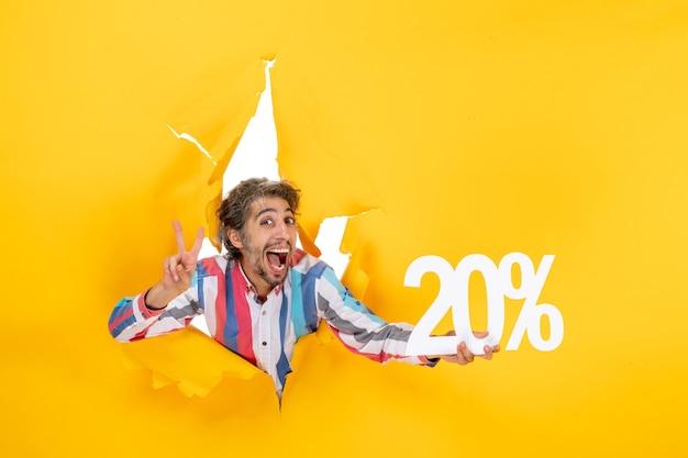 Bovenaanzicht van een lachende jongeman die twintig procent vasthoudt en een overwinningsgebaar maakt in een gescheurd gat in geel papier
