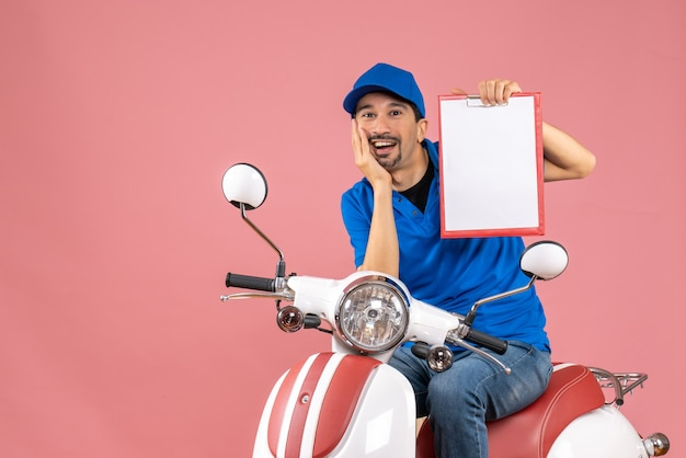 Bovenaanzicht van een lachende koeriersman met een hoed die op een scooter zit en een document toont op pastel perzik