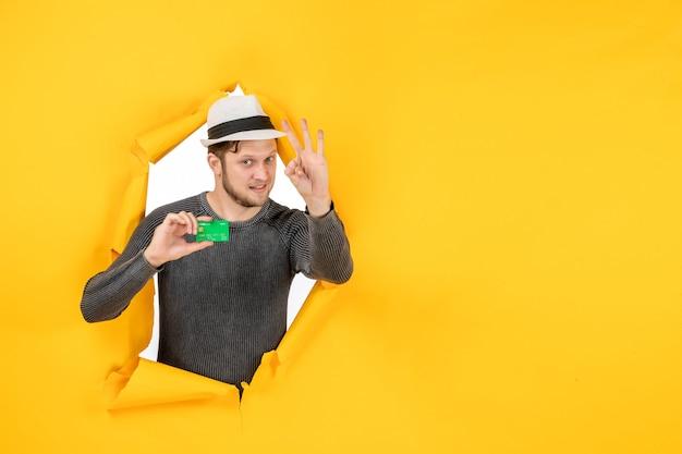 Bovenaanzicht van een lachende man die een bankkaart vasthoudt en drie in een gescheurde gele muur laat zien