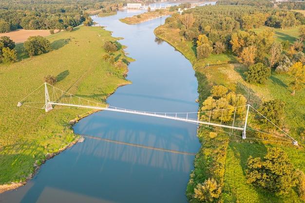 Bovenaanzicht van een lange voetgangersbrug over de blauwe rivier de odra, polen. moderne hangbrug