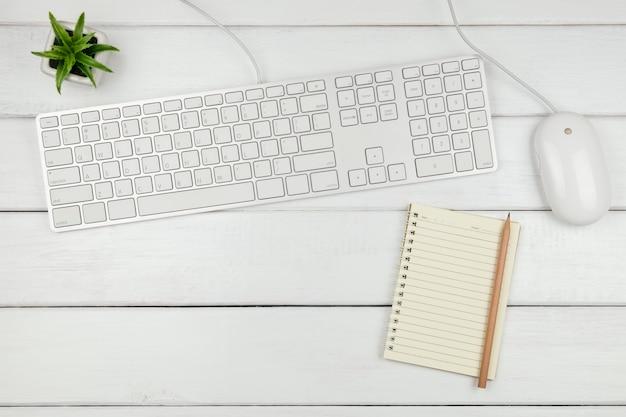 Bovenaanzicht van een laptop met toetsenbord en muis op wit bureau