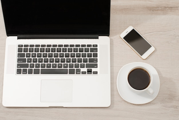 Bovenaanzicht van een laptop, smartphone en een kopje koffie