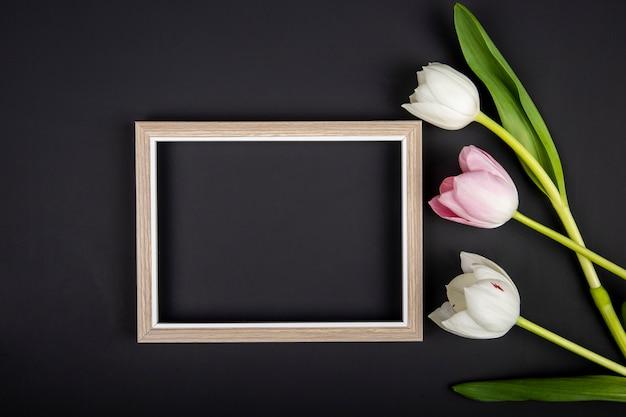 Bovenaanzicht van een leeg afbeeldingsframe en witte en roze kleur tulpen op zwarte tafel met kopie ruimte