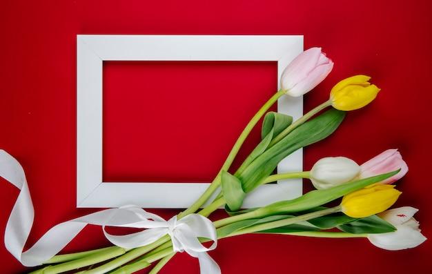 Bovenaanzicht van een leeg afbeeldingsframe met een boeket van kleurrijke tulp bloemen op rode achtergrond met kopie ruimte