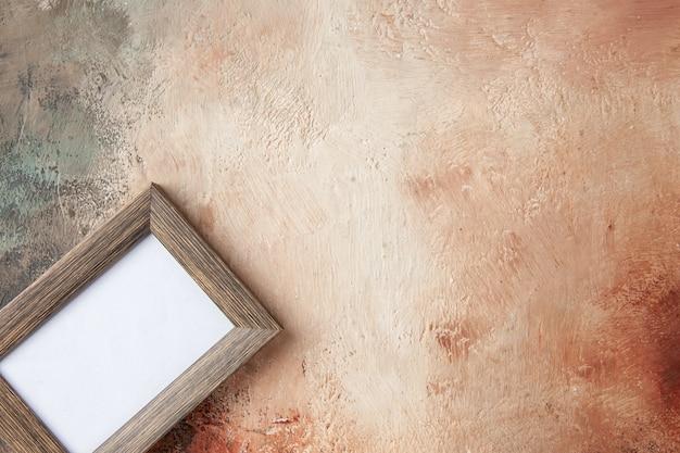 Bovenaanzicht van een leeg fotolijstje opgehangen aan een gemengde kleurenmuur met vrije ruimte