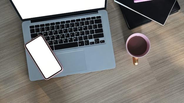 Bovenaanzicht van een leeg scherm laptop, mobiele telefoon, koffiekopje en notebook op houten tafel.