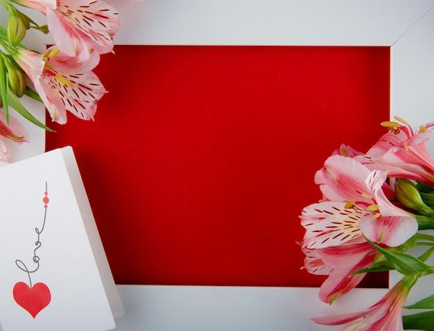 Bovenaanzicht van een lege witte fotolijst met roze kleur alstroemeria bloemen en een briefkaart op rode achtergrond met kopie ruimte